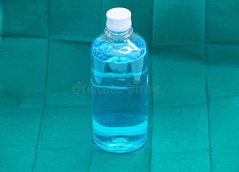 Blue ethyl alcohol liquid in plastic transparent bottle on green royalty free stock image