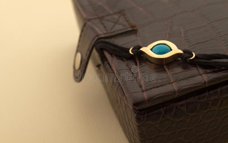 Blue eye golden bracelet on leather jewelry box royalty free stock images