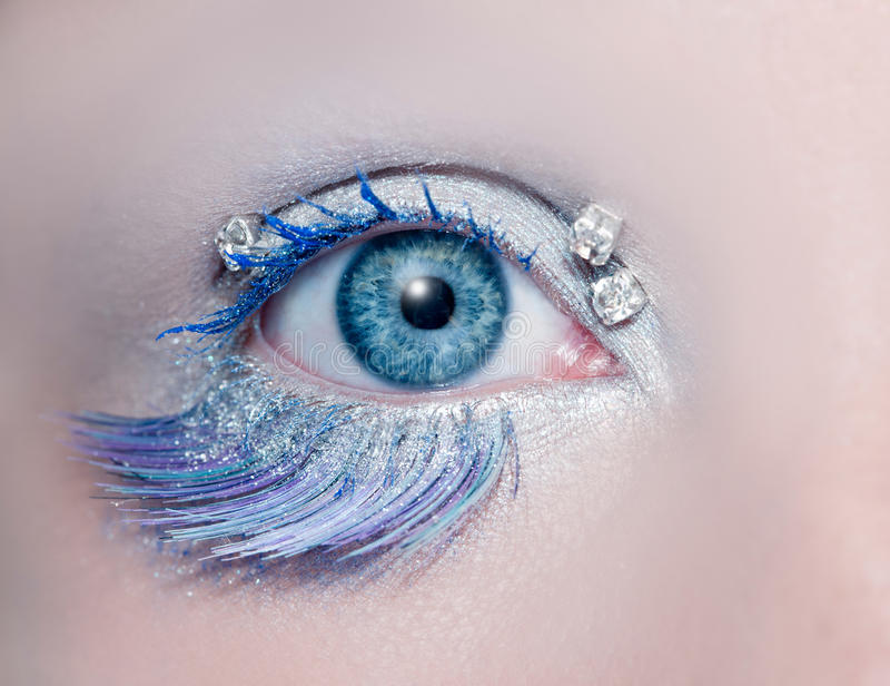Blue eye macro closeup winter makeup. Blue eye macro closeup with a winter inspired silver makeup some jewels and feather eyelashes royalty free stock images