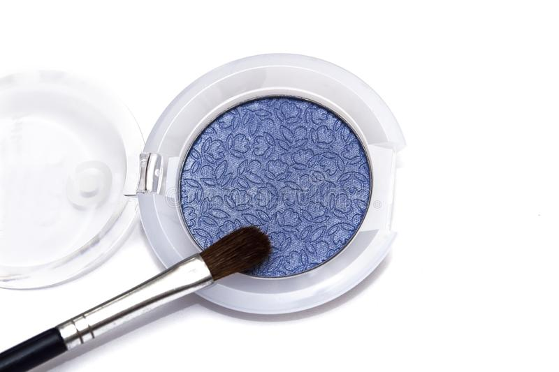 Blue eye shadows and eye brush crushed samples isolated on white background. Blue eye shadows and eye brush  isolated on white background. Concept of makeup and royalty free stock image