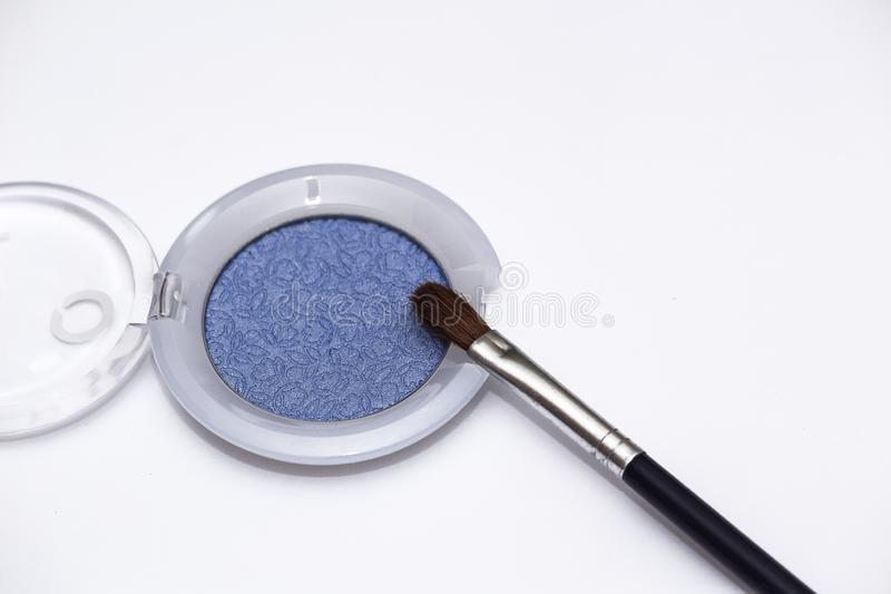 Blue eye shadows and eye brush isolated on white background. Concept of makeup and beauty stock photo