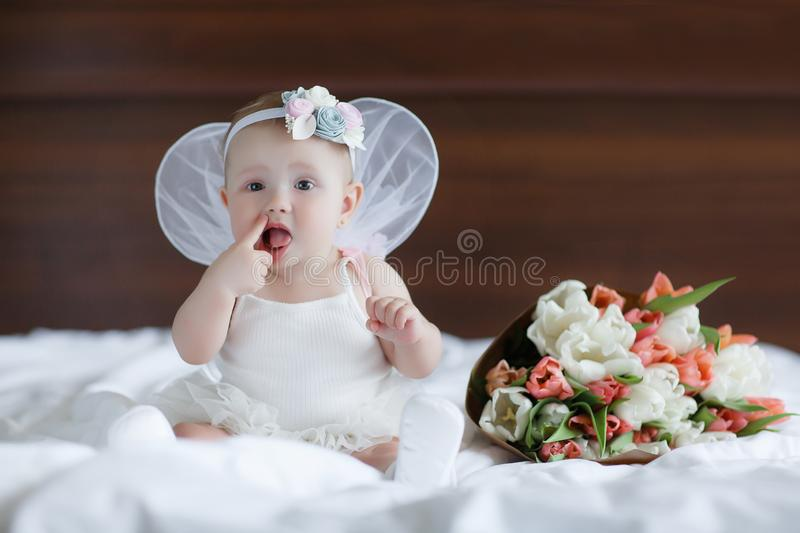 Happy little baby with angel wings. Blue-eyed baby with angel wings behind him.Baby Newborn with Angel Wings. Child Sitting at Blue Sky Cloud. Girl 5-7 months stock images