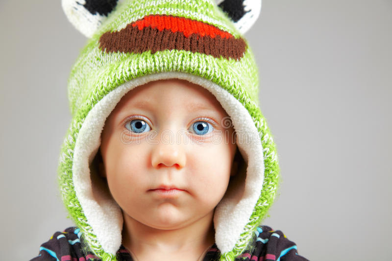 Blue eyed baby boy. Portrait of a cute little adorable child with funny green hat over gray background stock photography