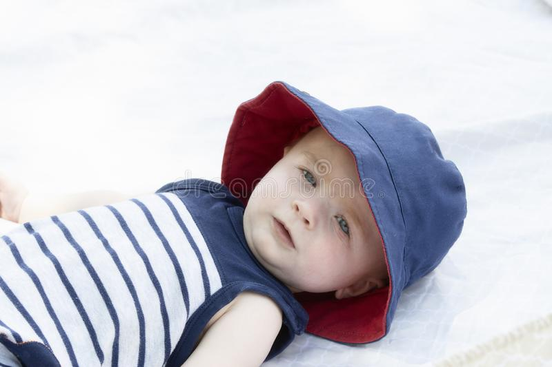 Blue-eyed Baby Boy Lying on Back Outside on Blanket with Hat royalty free stock photo