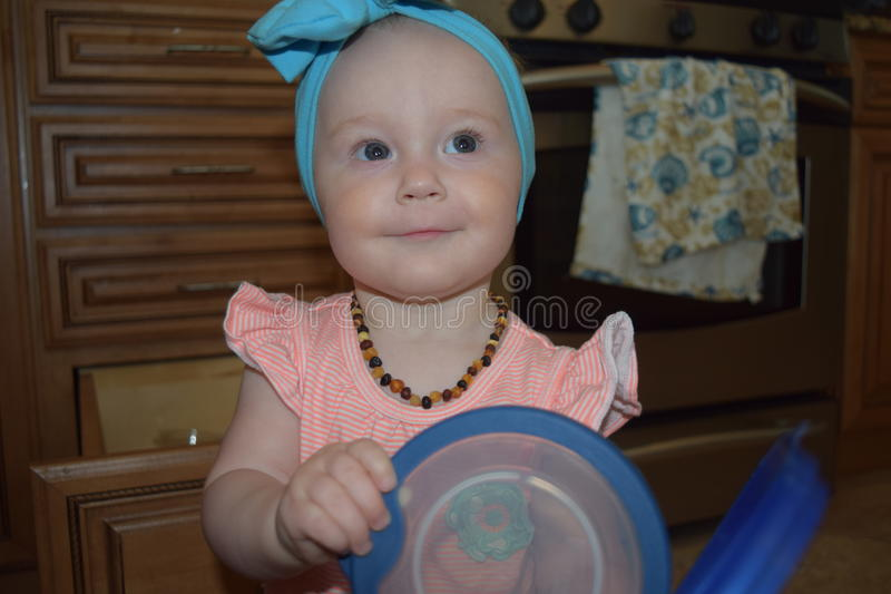 Blue eyed baby girl with tupperware. Baby girl with blue eyes and blue bow in kitchen holding tupperware stock photo