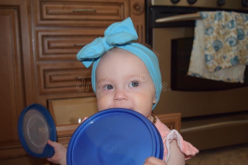 Blue eyed baby girl with tupperware. Baby girl with blue eyes and blue buy chewing on tupperware/teething stock images