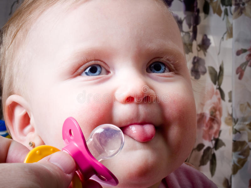 Blue-eyed Baby grabbing binky royalty free stock images