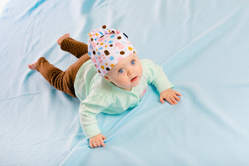 Blue-eyed baby in hat crawling stock images