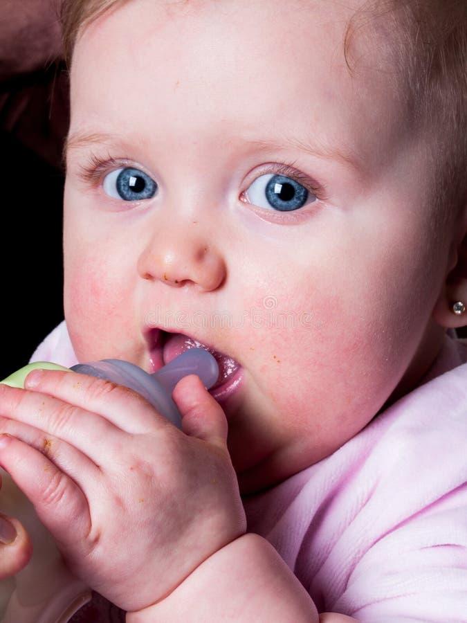 Blue-eyed Baby sucking bottle stock image