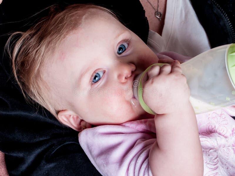 Blue-eyed Baby sucking bottle stock photos