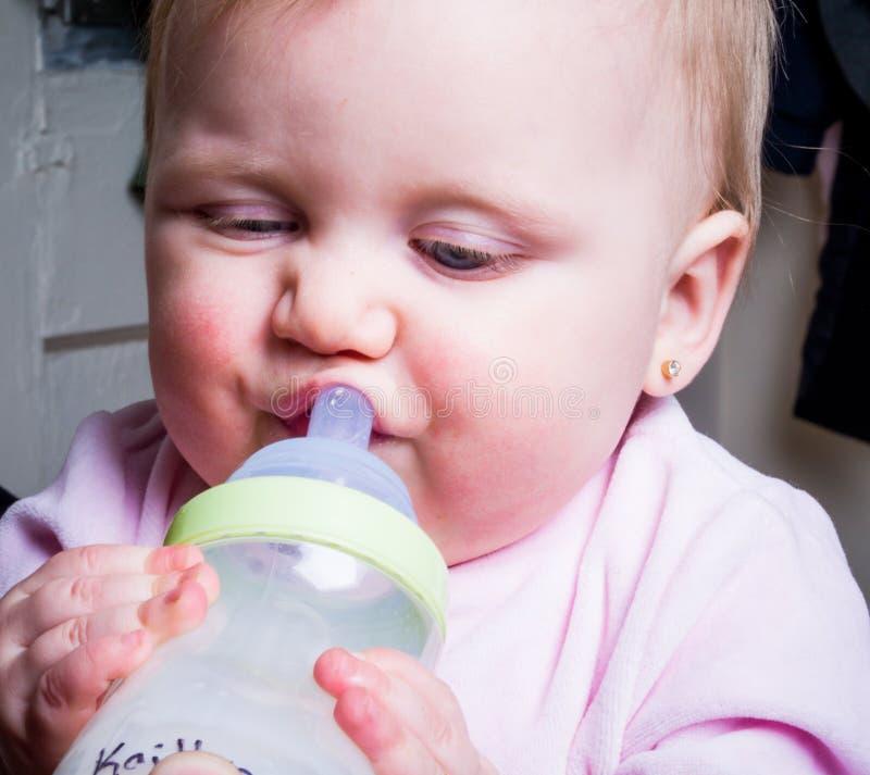 Blue-eyed Baby sucking bottle stock photography