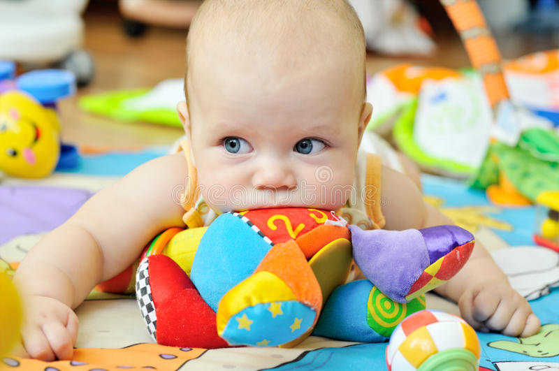 Blue-eyed baby with toys royalty free stock photo