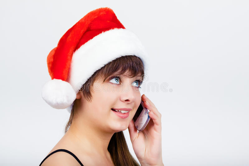 Blue-eyed beautiful girl in santa hat with phone stock image