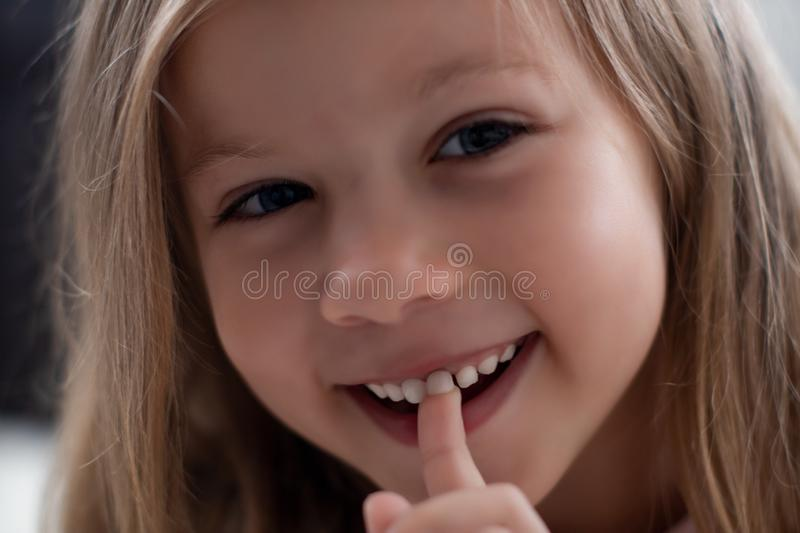 Blue-eyed blond girl laughs and shows the first tooth. children`s teeth, loss royalty free stock photo