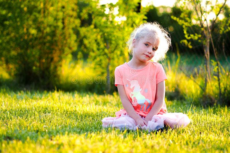 Blond blue eyed little girl playing in the park royalty free stock photos
