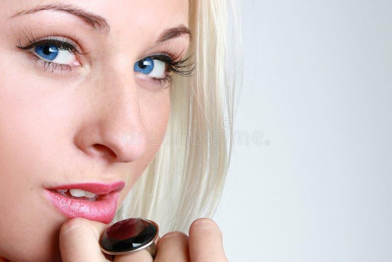 Blue-eyed blonde. Half face of the blue-eyed blonde stock photo