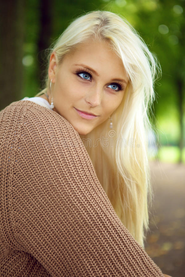 Blue-eyed Blonde Beauty. A beautiful blue-eyed young blonde woman gazes intently in to the distance in a park, close up face royalty free stock photos