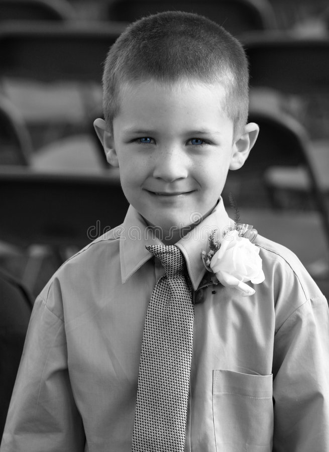 Blue Eyed Boy. A young boy in shirt, clip on tie and with a corsage cracks a nice smile. The photo is black and white but his eyes are a deep blue. If you like royalty free stock photos