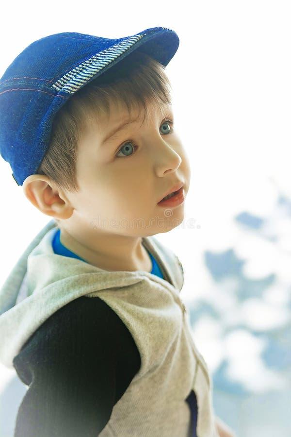 Blue-eyed boy in a denim cap royalty free stock image