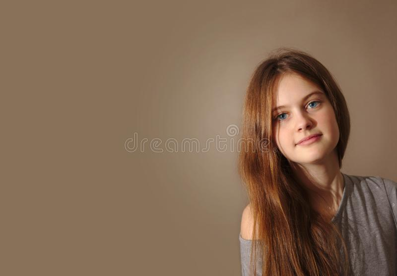 Blue eyed brown haired shy girl with flowing hair royalty free stock images