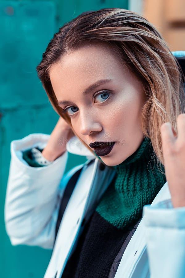 Blue-eyed fashion model with dark lipstick posing outside stock photos
