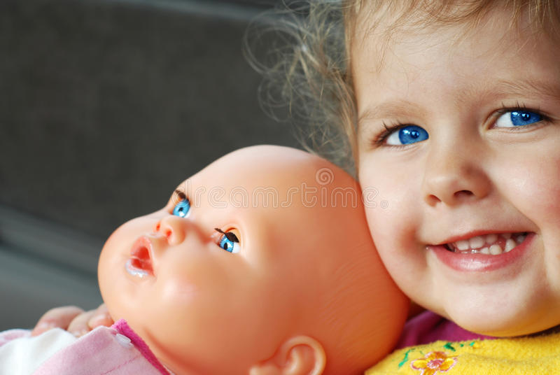 Blue-eyed girl with a doll stock photography