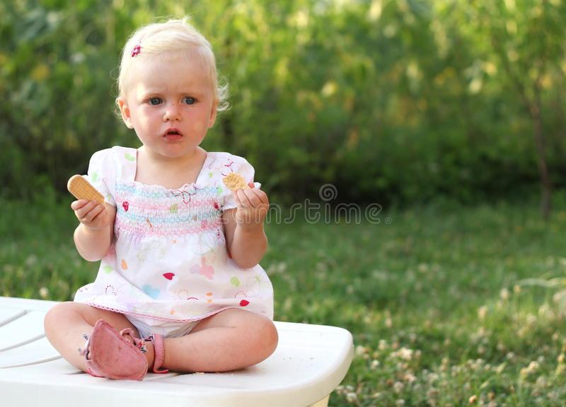 Blue eyed gorgeous baby girl. Blonde baby girl with crackers stock photo