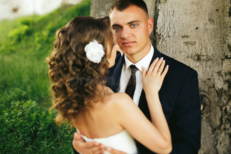 Blue-eyed groom looks thoughtful holding bride in his hugs. A stock images