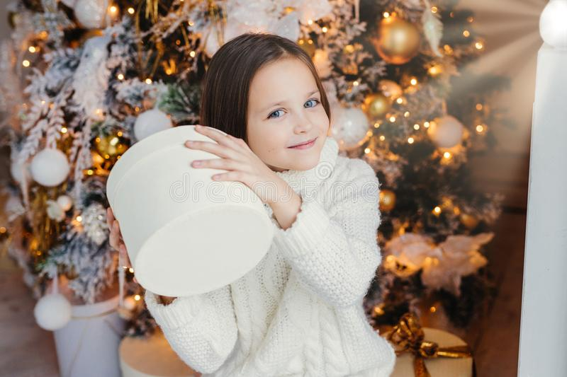 Blue eyed pretty lovely small child holds present box, wonders what is inside, stands near New Year or Christmas tree, recieves su royalty free stock photography