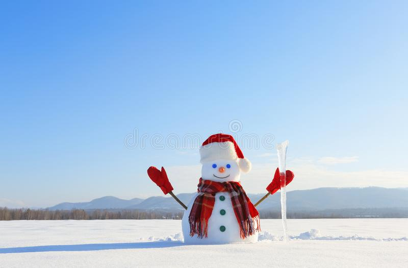 The blue eyed smiling snowman in red hat, gloves and plaid scarf holds the icicle in hand. Joyful cold winter morning. stock photos