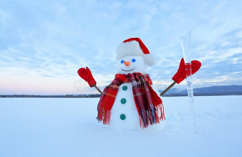 The blue eyed smiling snowman in red hat, gloves and plaid scarf holds the icicle in hand. Joyful cold winter morning. stock photo