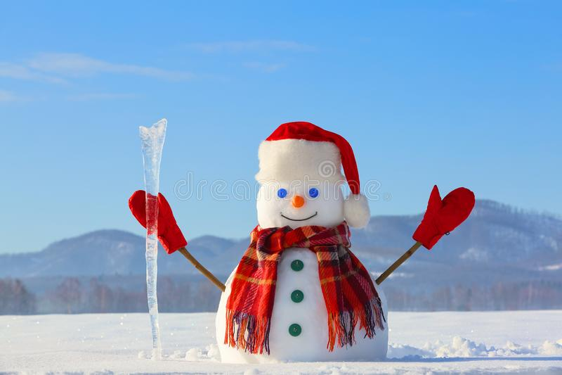 The blue eyed smiling snowman in red hat, gloves and plaid scarf holds the icicle in hand. Joyful cold winter morning. royalty free stock photo