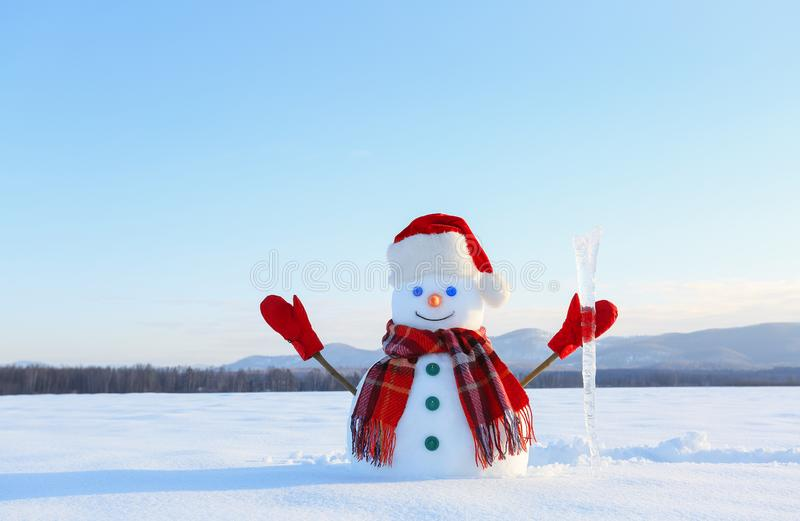 The blue eyed smiling snowman in red hat, gloves and plaid scarf holds the icicle in hand. Joyful cold winter morning. royalty free stock photos