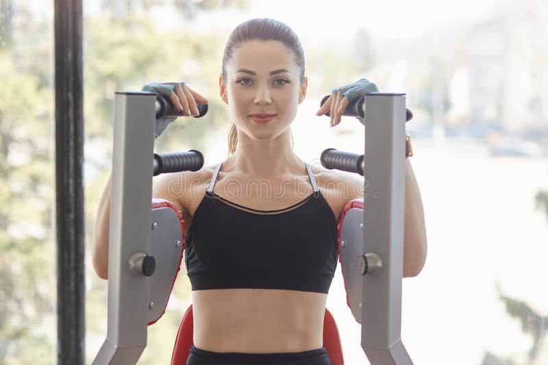 Blue eyed strong European woman spends her free time in gym, does work sets, looks directly at camera, seems to be pleased. royalty free stock photography