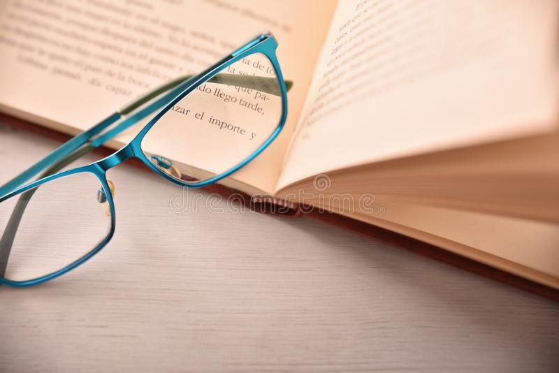 Blue eyeglasses on open book on white table top. Detail of eyeglasses on open book on white table .Concept need glasses to read. Top view. Horizontal composition royalty free stock photography