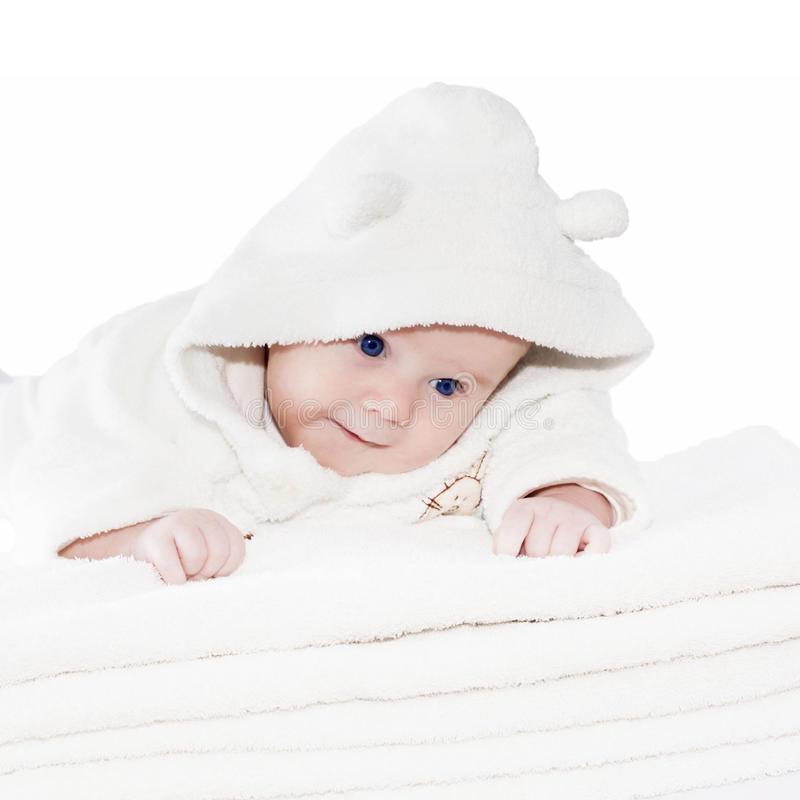 Blue eyes baby boy on white towels. Newborn baby boy with blue eyes crawling on a pile of white towels. Closeup, Isolated on white background royalty free stock photo