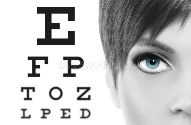 blue eyes close up on visual test chart, eyesight and eye examination concept in white background royalty free stock photography