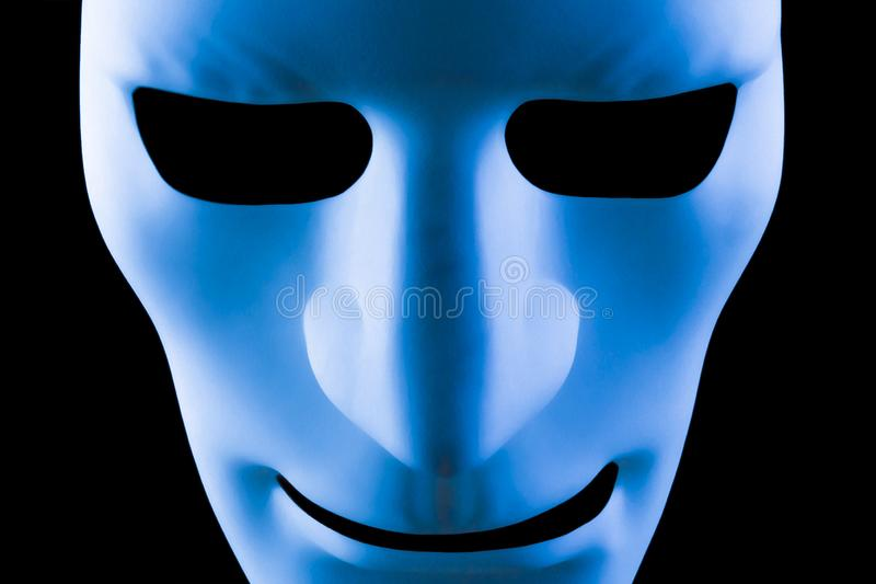 Blue face artificial intelligence robot. Blue face mask artificial intelligence concept close up on a black background royalty free stock images