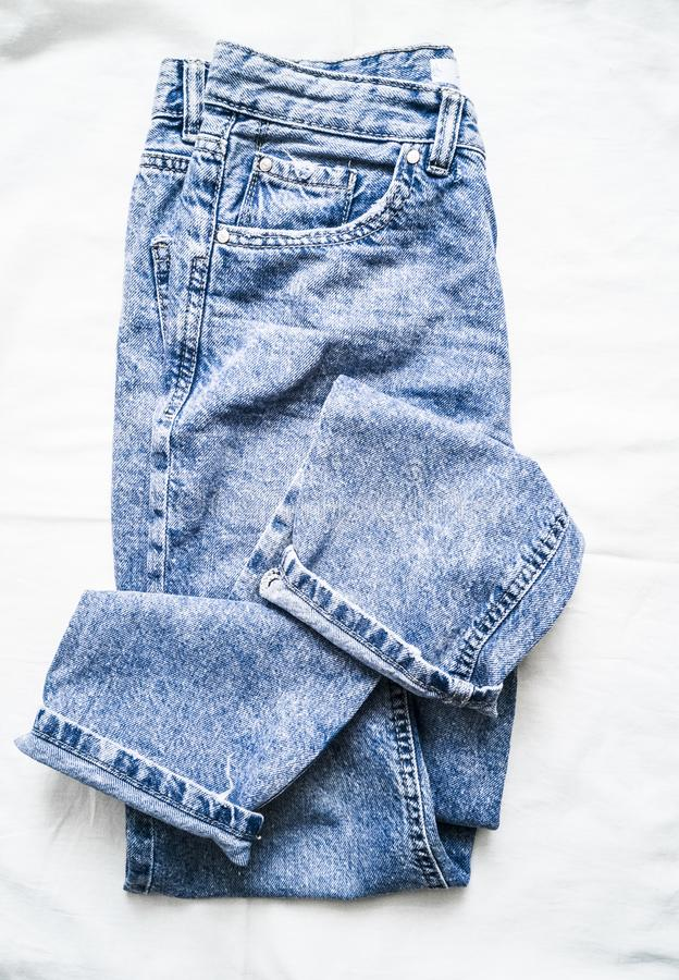 Blue faded mom jeans on a light background, top view. Fashion clothing royalty free stock photography