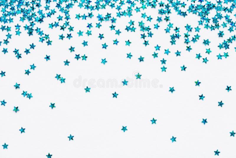 Blue falling stars glitter confetti on white festive background Sparkling Frame stock photo