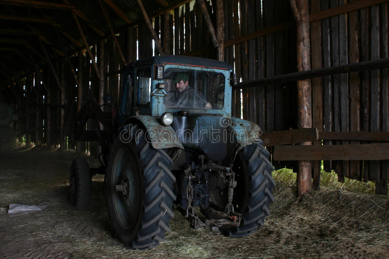 Blue farm tractor with tractor driver, under roof of hayloft. Lemozero, Olonets, Karelia, Russia - July 26, 2006: Blue farm tractor, with the driver of the stock photo