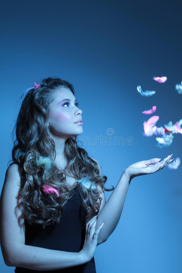 Blue fashion shoot of young woman and feathers. Beautiful blue fashion shoot of young woman and feathers stock images