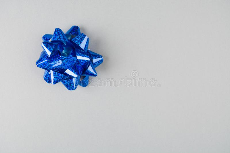 Blue festive bow over grey paper background stock photo