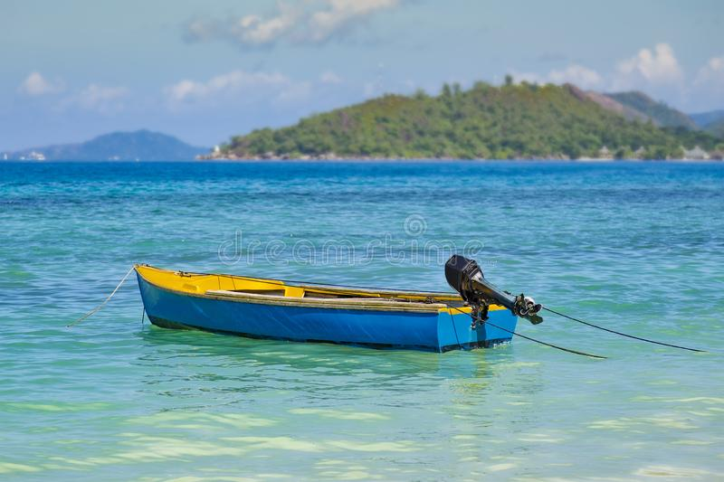 Blue fishing boat with outboard motor on turquoise ocean. Colorful small blue fishing boat with outboard motor anchoring in turquoise ocean, shallow depth of royalty free stock images