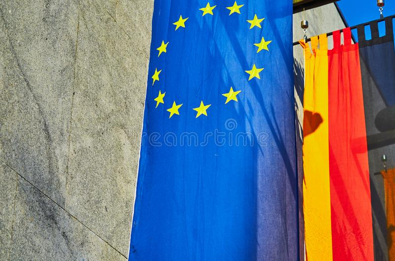 Blue flag with yellow stars of the European Union EU in front of the black and red golden flag of the Federal Republic of. Germany royalty free stock image