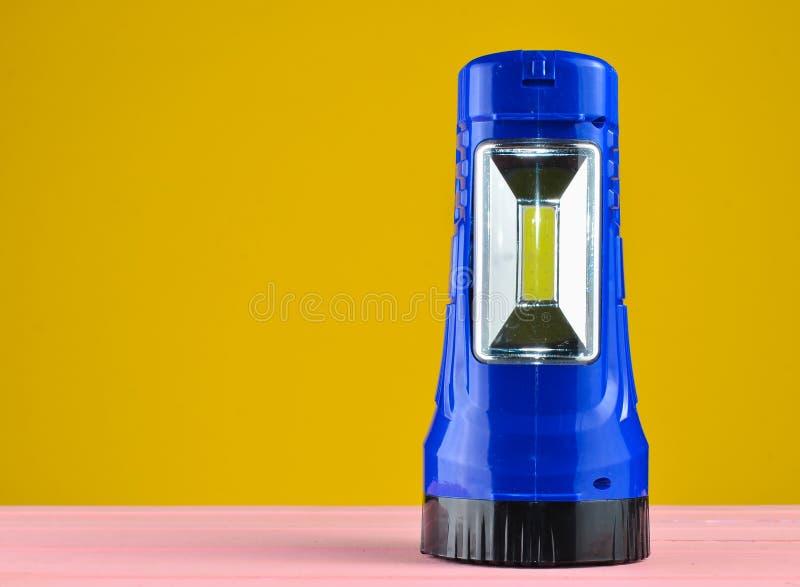 Blue flashlight projector lies on a desk isolated on a yellow wall. Blue flashlight projector lies on a desk isolated on a yellow wall royalty free stock photo