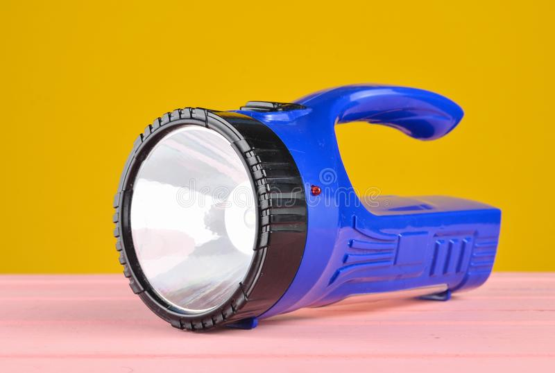 Blue flashlight projector lies on a desk isolated on a yellow wall. Blue flashlight projector lies on a desk isolated on a yellow wall royalty free stock photos