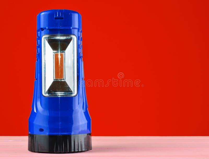 Blue flashlight projector lies on a desk isolated on a yellow wall. Blue flashlight projector lies on a desk isolated on a yellow wall stock photography