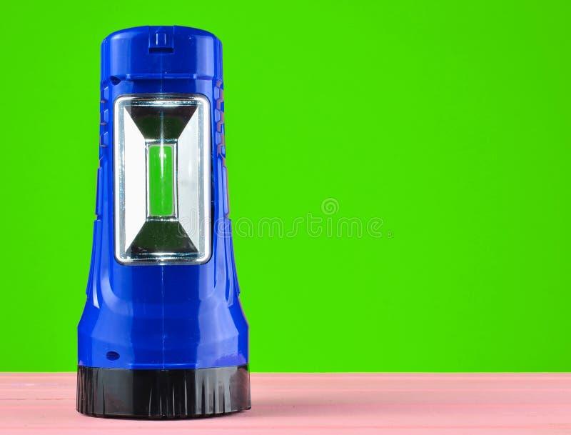 Blue flashlight projector lies on a desk isolated on a yellow wall. Blue flashlight projector lies on a desk isolated on a yellow wall stock photo