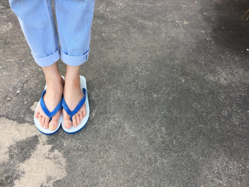 Blue Flip Flop on Cement Floor,Top view. Beautiful Woman Wearing Blue Shoes and Jeans of Accessory on Concrete Background. Great For Any Use royalty free stock image